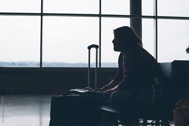 Man waiting at airport lounge by GIC for Stocksy United