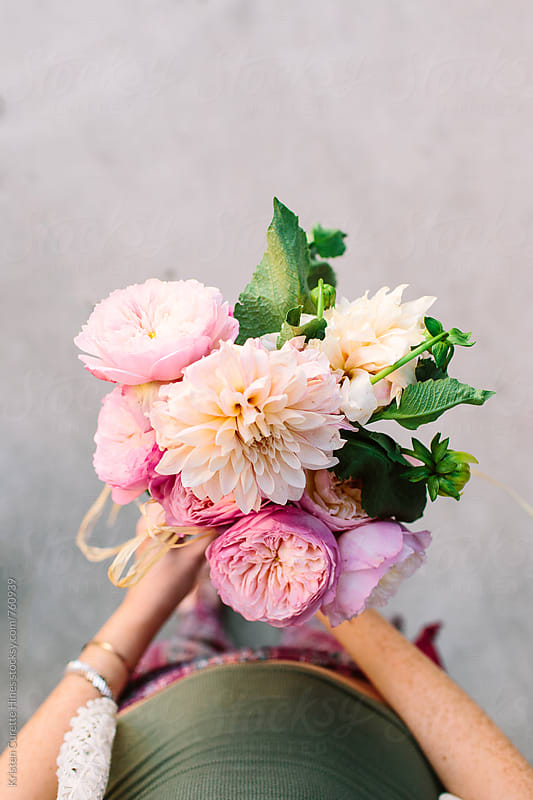 A first person view of someone holding a dahlia & garden rose arrangement.  by Kristen Curette Hines for Stocksy United