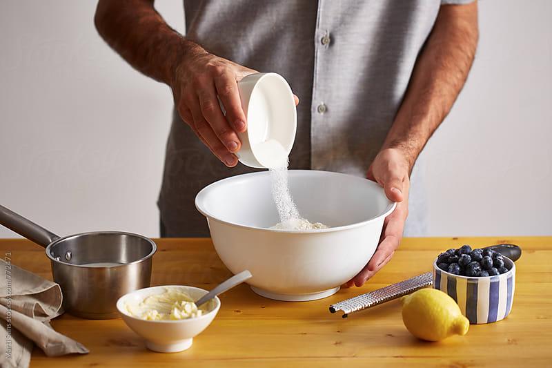 Preparing homemade blueberry rolls by Martí Sans for Stocksy United