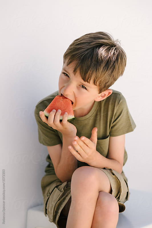 Child bites into a slice of watermelon by Rebecca Spencer for Stocksy United