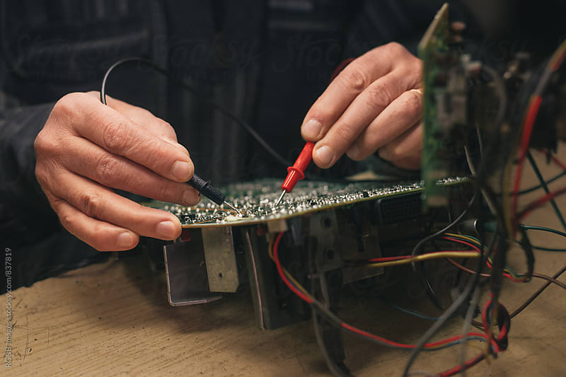 Tehnician probing a circuit board  by RG&B Images for Stocksy United