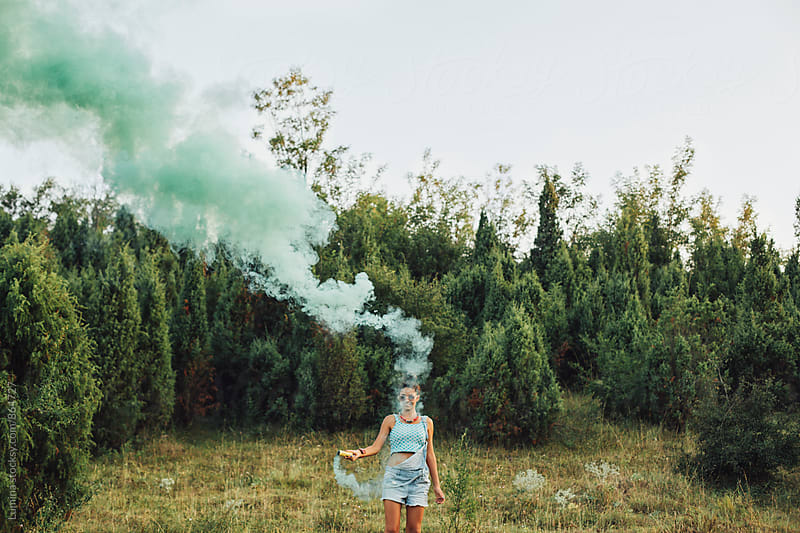 Happy Girl With a Green Smoke Bomb by Lumina for Stocksy United