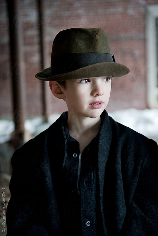 Portrait of a young boy wearing an old hat by Cara Slifka for Stocksy United