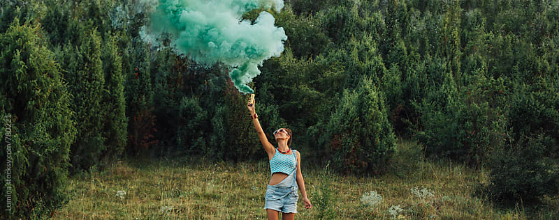 Woman Holding a Smoke Bomb by Lumina for Stocksy United