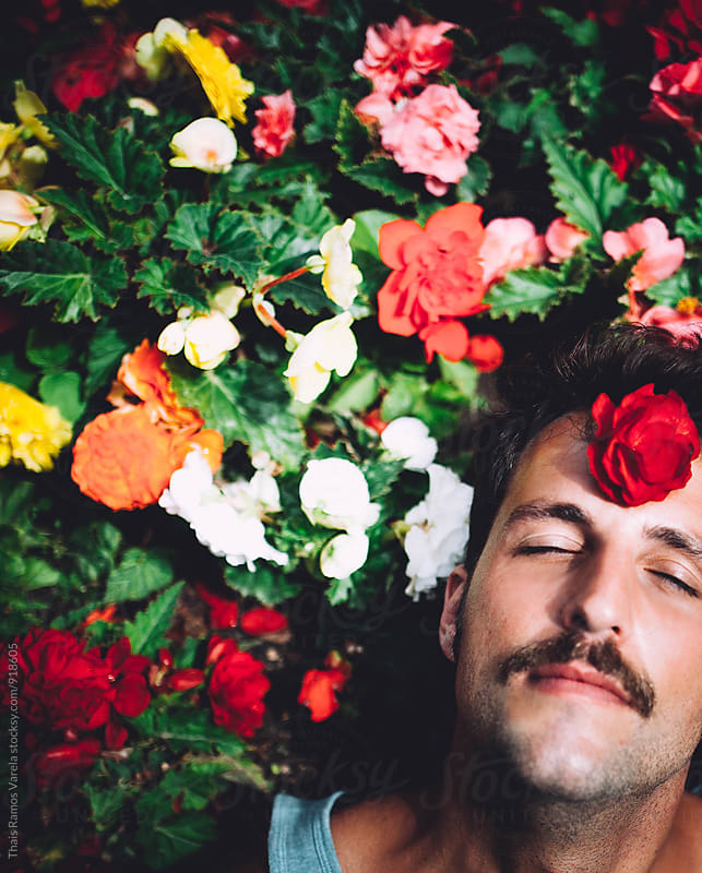 Man with flowers around  by Thais Ramos Varela for Stocksy United
