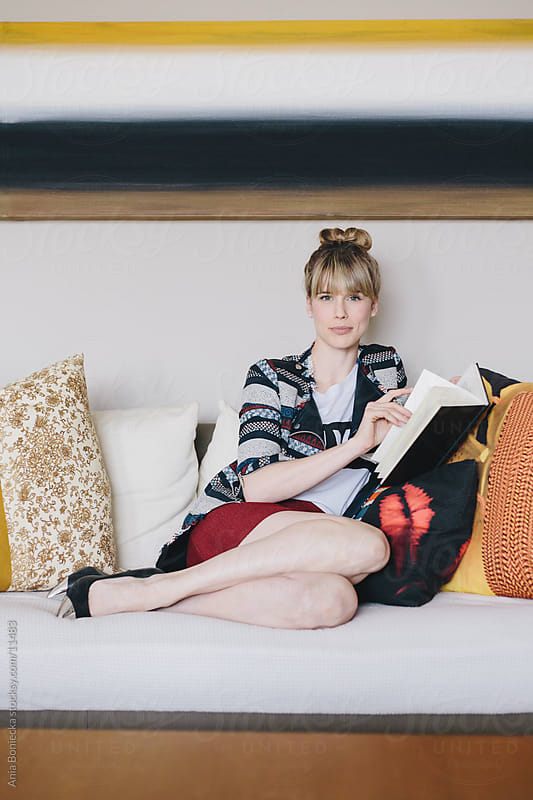 A beautiful blonde reading a book on the sofa by Ania Boniecka for Stocksy United