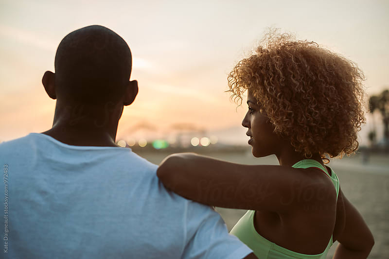 Young attractive black couple at the beach at sunset by Kate Daigneault for Stocksy United