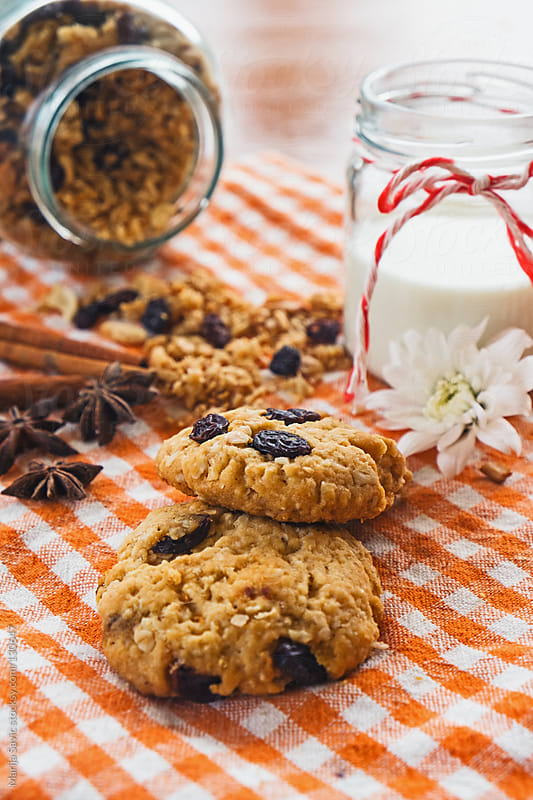 Oat cookies, milk and granola served on wooden table. by Marija Savic for Stocksy United