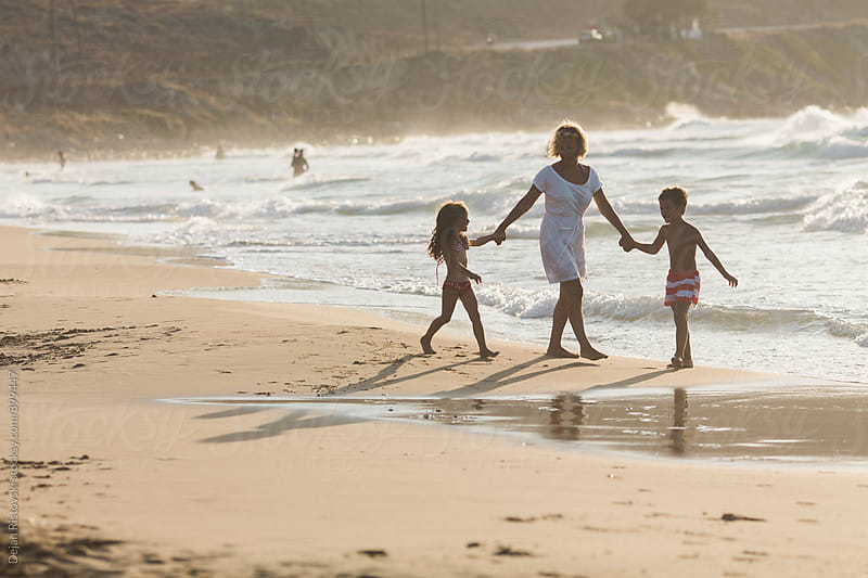 Family walking on the beach. by Dejan Ristovski for Stocksy United
