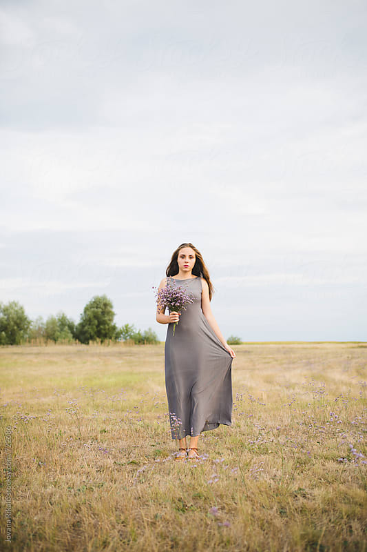 Beautiful young woman standing in a field and holding flower bouquet by Jovana Rikalo for Stocksy United