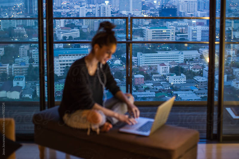 Woman working from her laptop - focus on the city behind her by Jovo Jovanovic for Stocksy United
