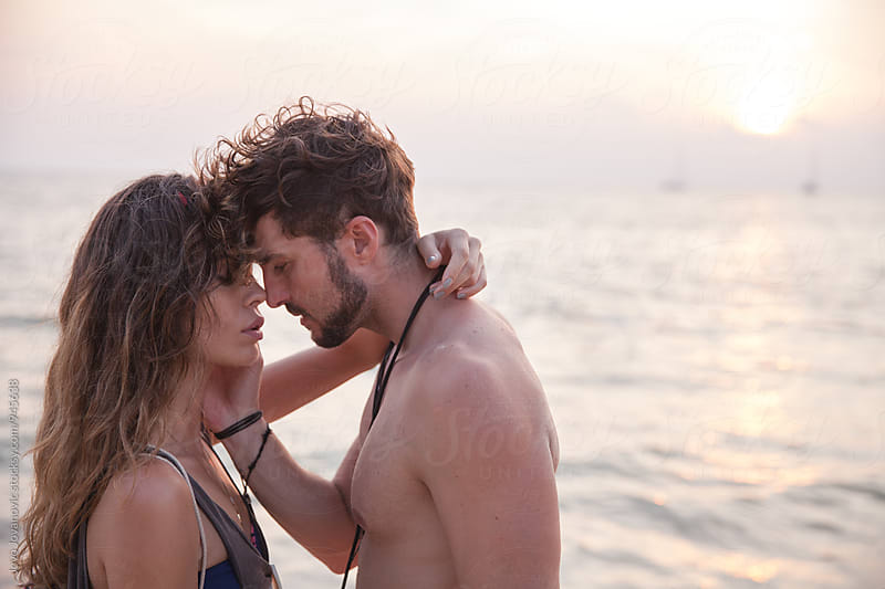 Sensual portrait of young couple at the beach by Jovo Jovanovic for Stocksy United