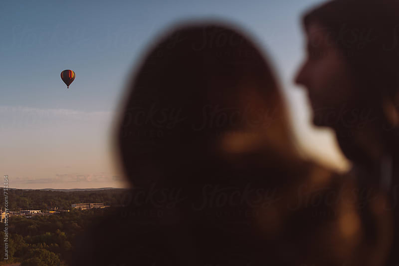Couple watching hot air balloon in the sky by Lauren Naefe for Stocksy United