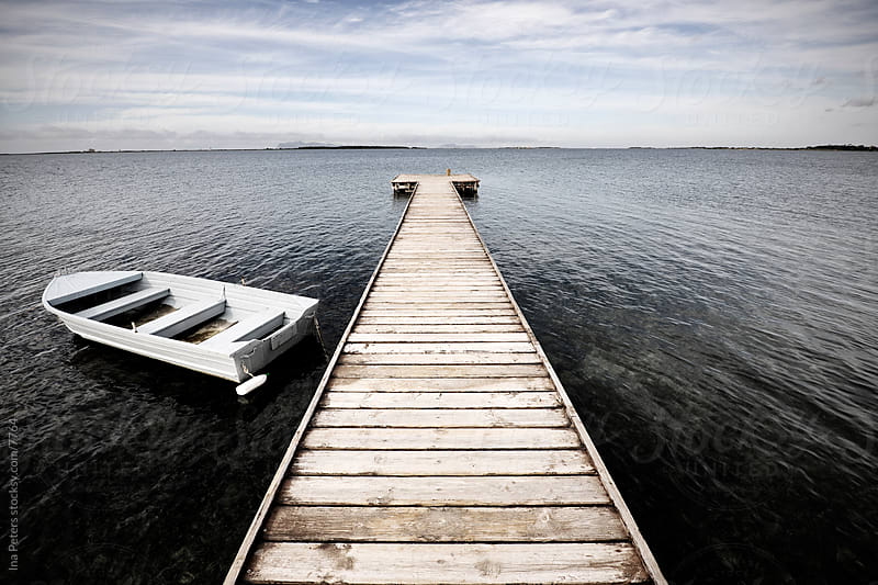 Boat and Jetty at the sea by Ina Peters for Stocksy United