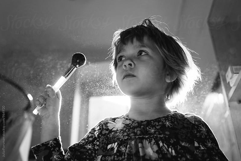 A little girl uses her mother's make up brush in morning light. by Julia Forsman for Stocksy United