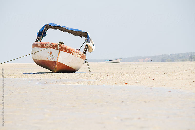 Old boat on the sand of a beach by Alejandro Moreno de Carlos for Stocksy United