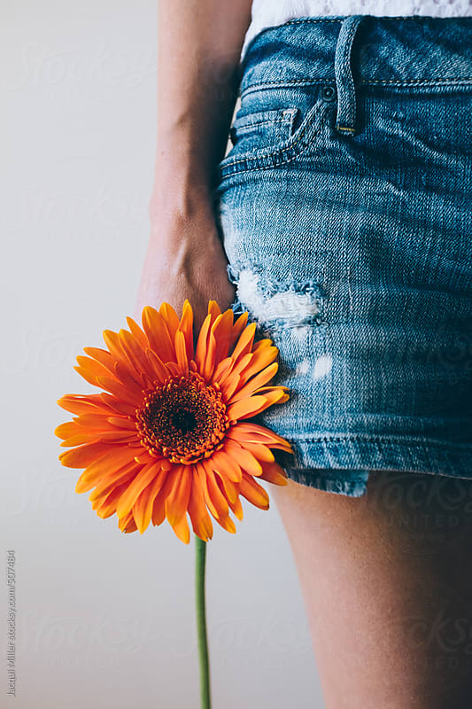 Woman holds an orange Gerbera flower in her hand next to denim shorts by Jacqui Miller for Stocksy United