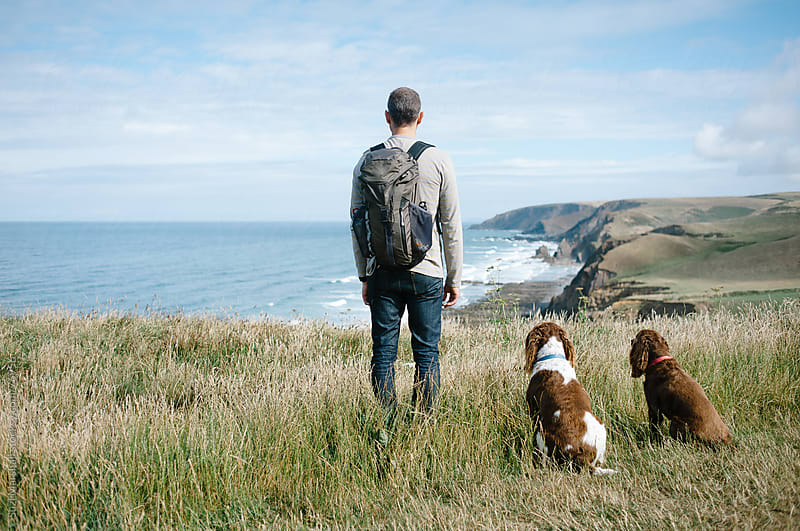 Man and two dogs standing on a cliff looking out to sea by Suzi Marshall for Stocksy United