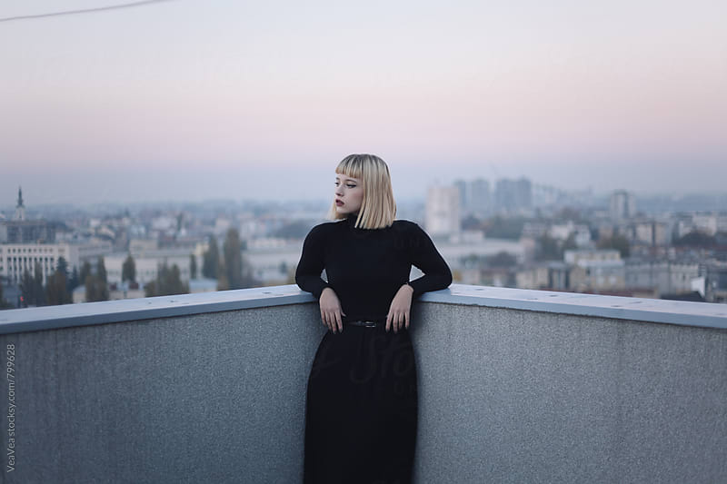 Portrait of a stylish blonde woman on the roof of the building during sunset by VeaVea for Stocksy United