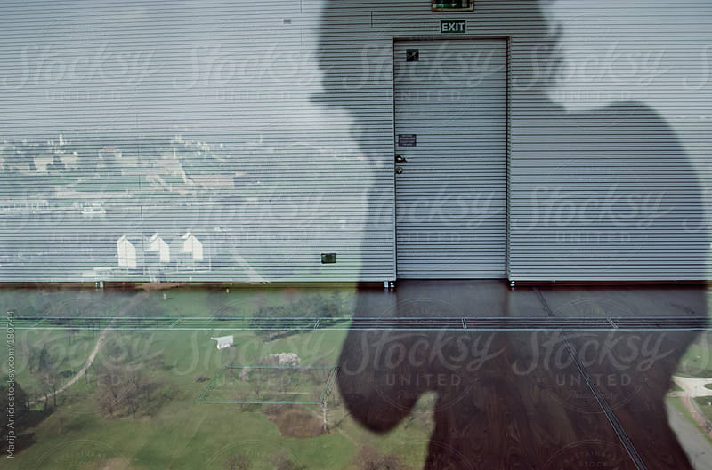 Reflection of town and silhouette of photographer on window by Marija Anicic for Stocksy United