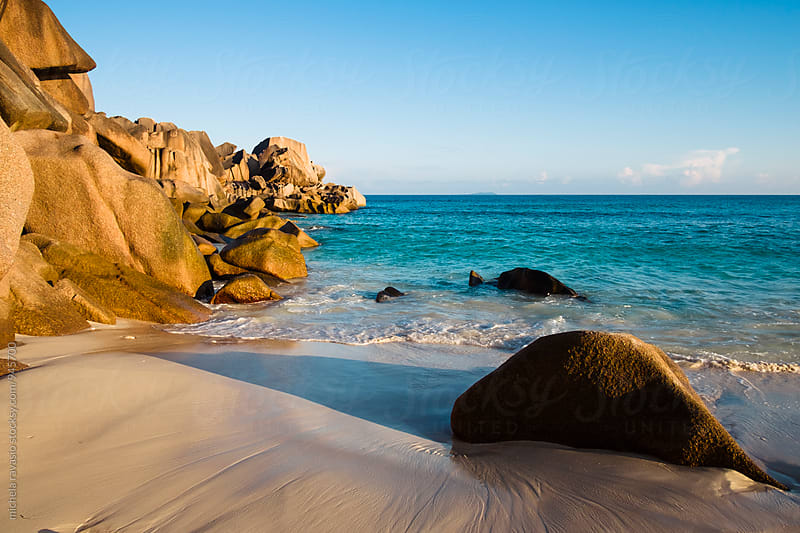 The sunset lights up the granite rocks of Grand Anse Beach, La Digue by michela ravasio for Stocksy United