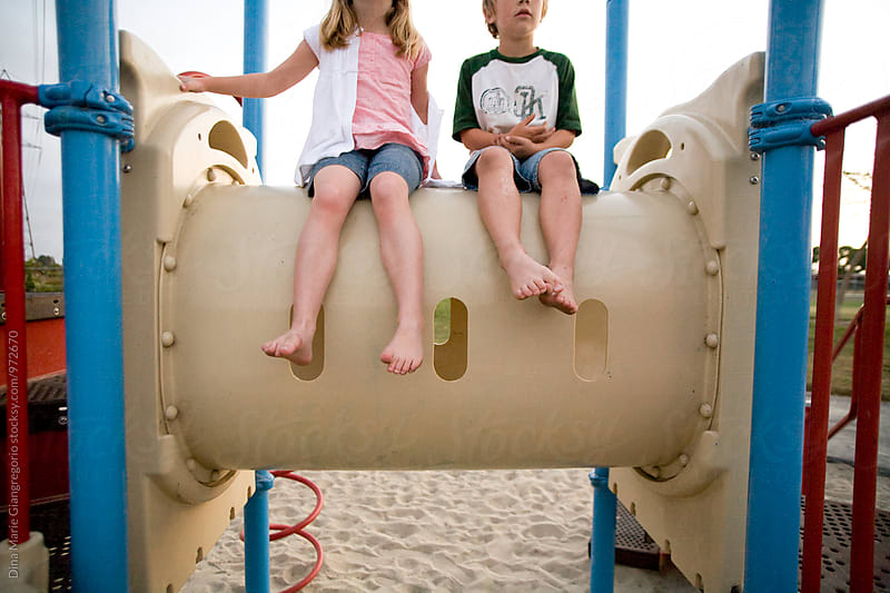Girl and Boy Sitting On Playground Equipment by Dina Giangregorio for Stocksy United