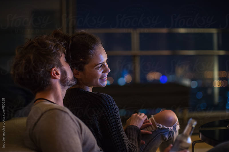 Young married couple sitting together and watching movie by Jovo Jovanovic for Stocksy United