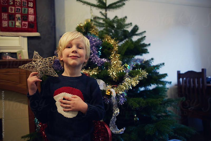 Child holding a Gold star for the Christmas tree by sally anscombe for Stocksy United
