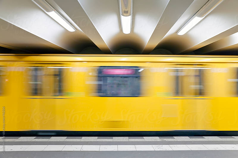 Europe, Germany, Berlin, modern subway station  - moving train pulling into the station by Gavin Hellier for Stocksy United