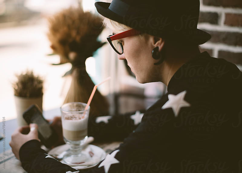 woman sitting in a coffee shop. by Alexey Kuzma for Stocksy United