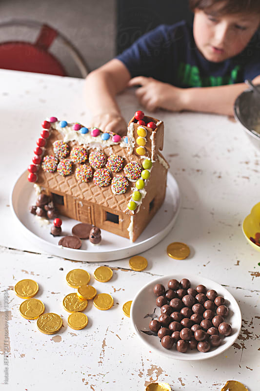Small boy decorates a gingerbread house with candy for Christmas by Natalie JEFFCOTT for Stocksy United