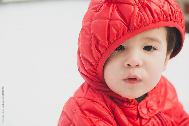 Baby in snowsuit looking at camera by Lauren Naefe for Stocksy United