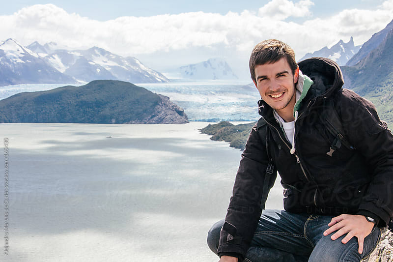 Young man portrait on glacier and mountain landscape in Patagonia by Alejandro Moreno de Carlos for Stocksy United