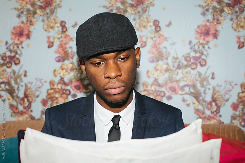 Headshot of Elegant Young Black Man Reading Newspaper by Julien L. Balmer for Stocksy United