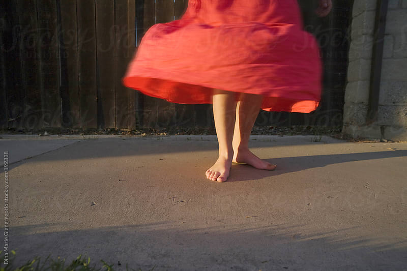Girl twirling coral colered skirt on sidewalk in golden summer light by Dina Giangregorio for Stocksy United