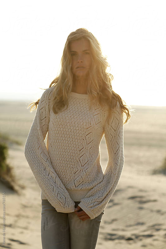 young woman on beach at sunset by Rene de Haan for Stocksy United