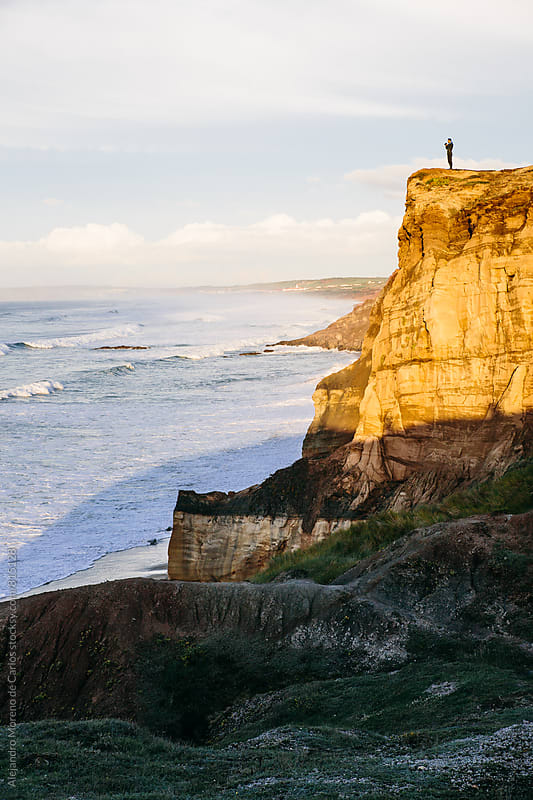 Person on top of a cliff illuminated by the sunset looking towards the sea and the waves by Alejandro Moreno de Carlos for Stocksy United