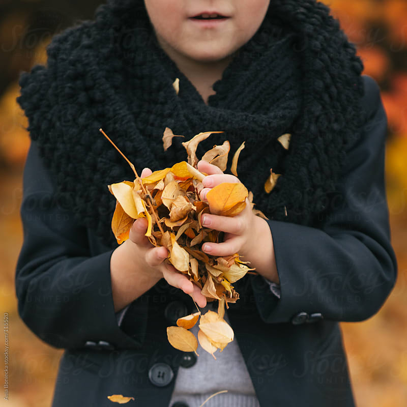 A boy holding a handful of leaves by Ania Boniecka for Stocksy United