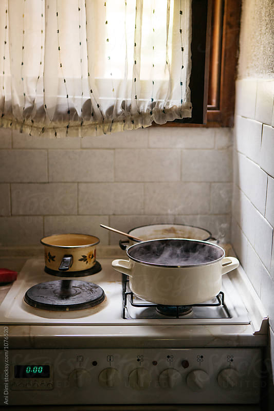 Copper pots on old stove by Ani Dimi for Stocksy United