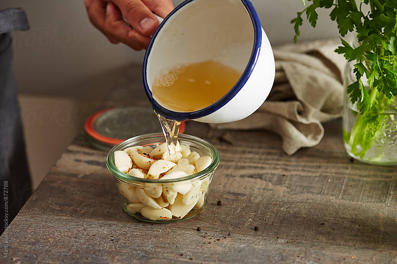 Man pouring heads of garlic with pickle by Martí Sans for Stocksy United