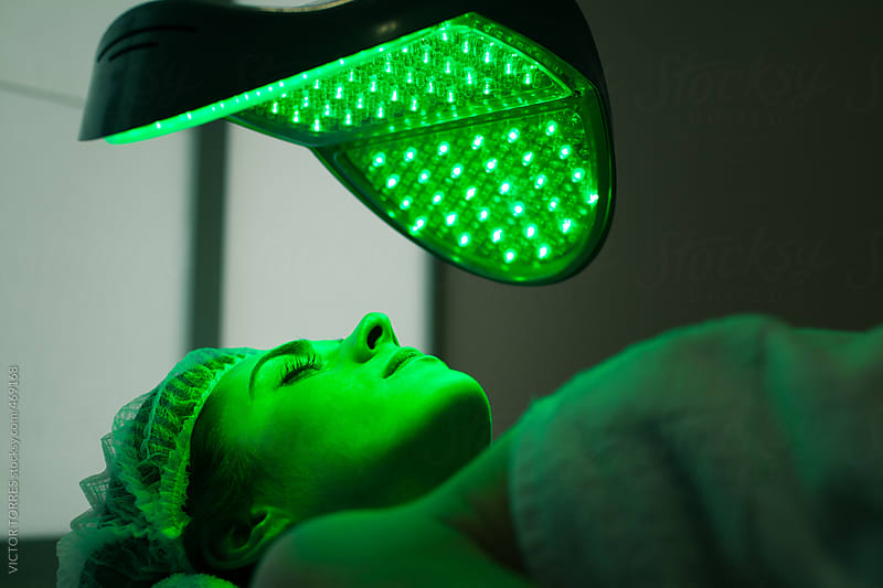 Woman in a Beauty Clinic Receiving a Facial Color Light Treatment by VICTOR TORRES for Stocksy United