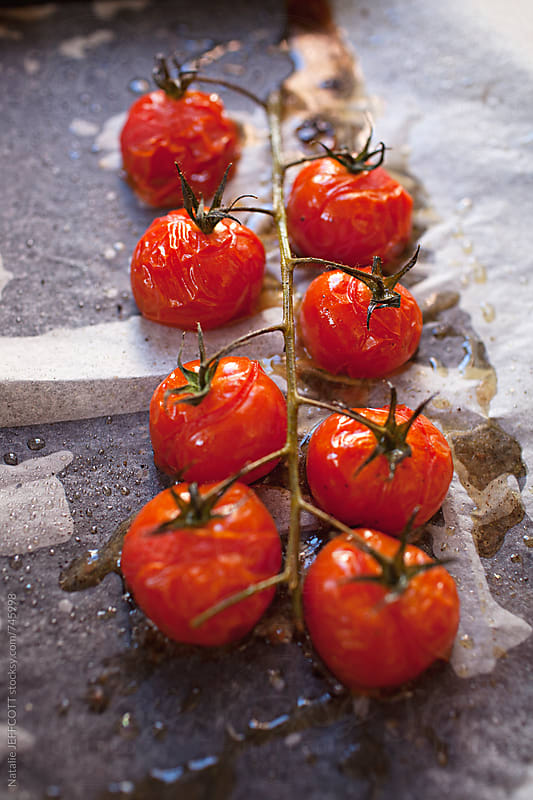 fresh roasted cherry tomatoes on a vine with oil and salt on baking paper by Natalie JEFFCOTT for Stocksy United