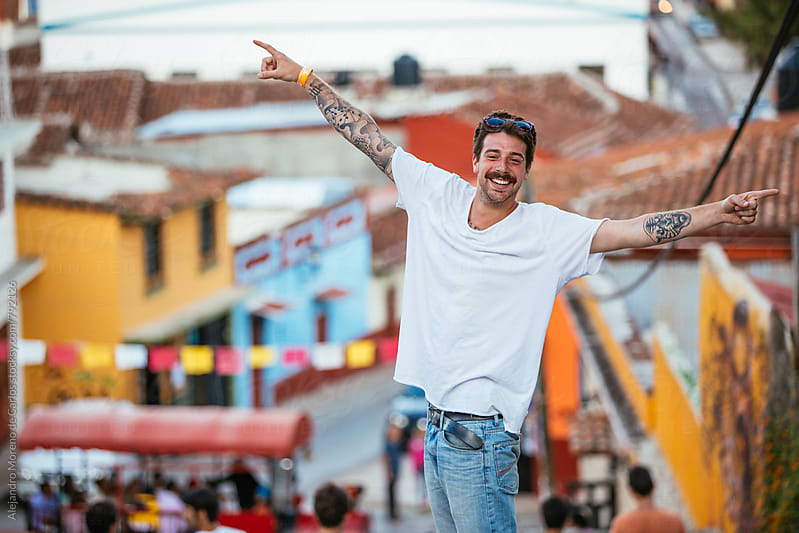Young happy hipster man with tattoos with his arms open on the top hill of a typical mexican town by Alejandro Moreno de Carlos for Stocksy United