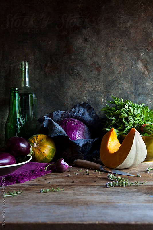 Still life of vegetables with pumpkin, eggplant, radish, herbs, cabbage, squash and flowering thyme on wood table by Nadine Greeff for Stocksy United