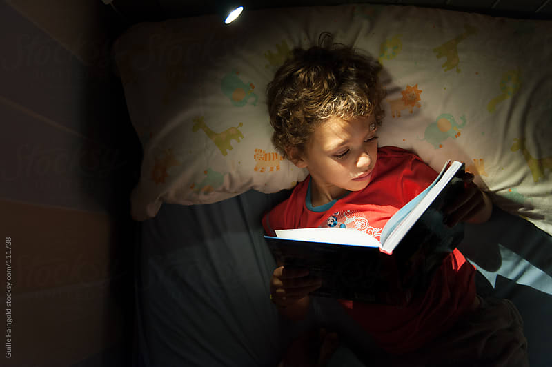 Above portrait of adorable kid reading book in bed. by Guille Faingold for Stocksy United