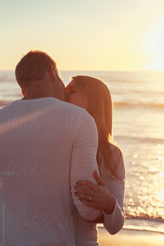 Young couple kissing and hugging on the beach at sunset by paff for Stocksy United