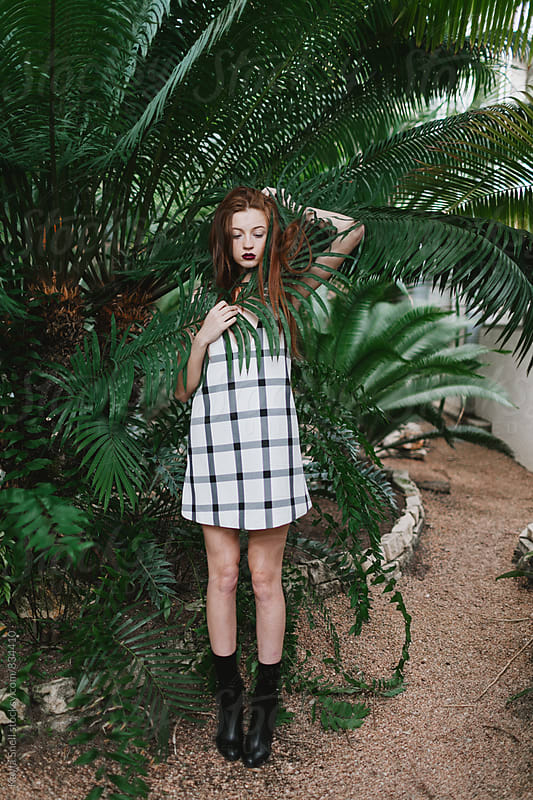 Woman hiding herself behind a plant by Kayla Snell for Stocksy United