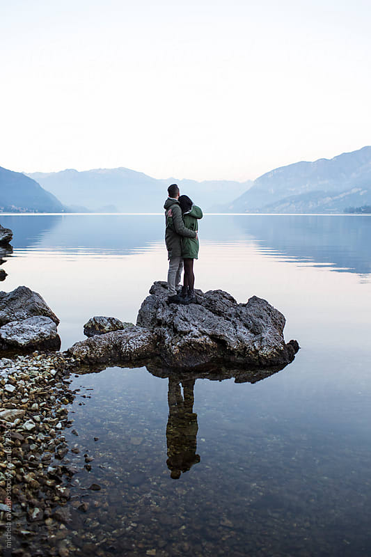 Young couple embracing on a rock by the lake by michela ravasio for Stocksy United