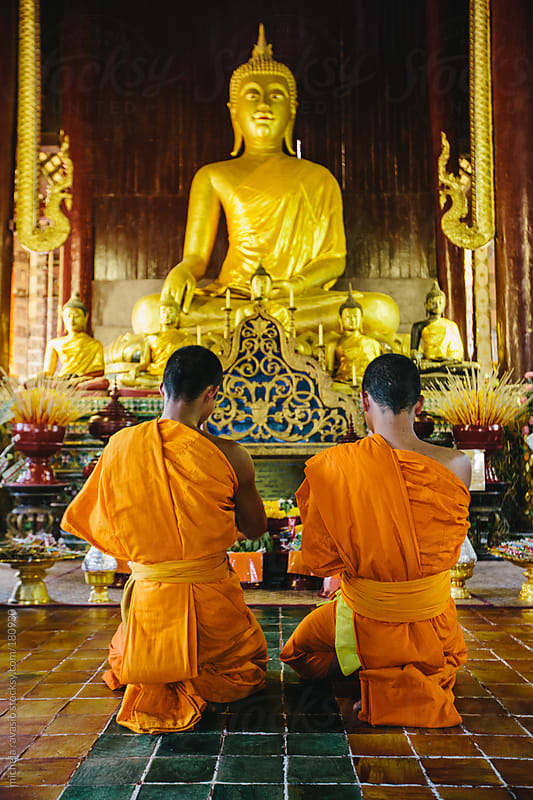 Two Buddhist monks praying in the temple by michela ravasio for Stocksy United