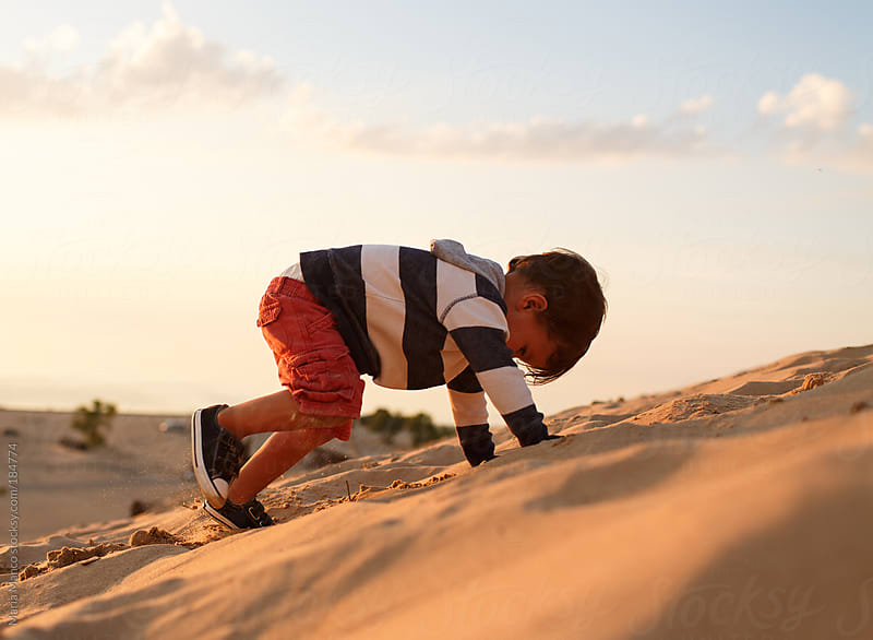child climbs up sand dune by Maria Manco for Stocksy United